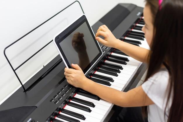 Uma menina aprende a tocar piano em aulas de vídeo. aprendizagem à distância online durante covid-19