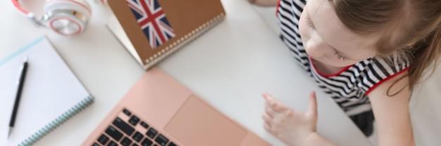 Uma menina aprende línguas estrangeiras no laptop