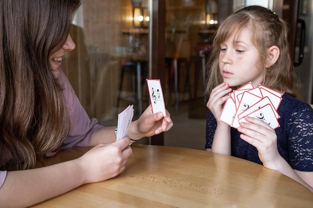 Uma menina aprende notas de forma lúdica, com a ajuda de cartas musicais especiais Foto gratuita