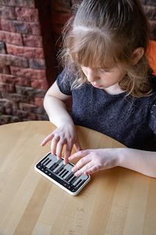 Uma menina aprende notas de forma lúdica, com a ajuda de um piano em seu telefone