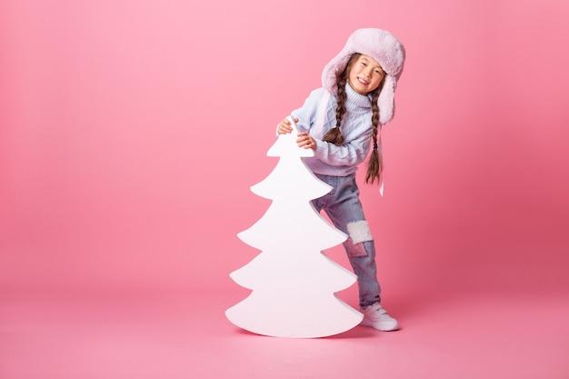 Uma menina asiática bonitinha com um chapéu de inverno está ao lado de uma árvore de natal em um fundo rosa. conceito de inverno, espaço para texto