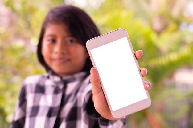Uma menina asiática bonitinha mostrando smartphone com tela branca em branco