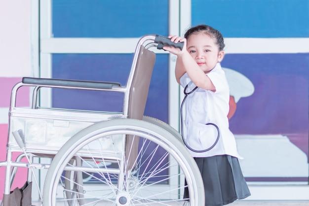 Uma menina asiática bonito e adorável no vestido uniforme de enfermeira segurando a cadeira de rodas