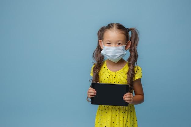 Uma menina asiática com uma máscara no rosto segura um tablet nas mãos no estúdio em um azul