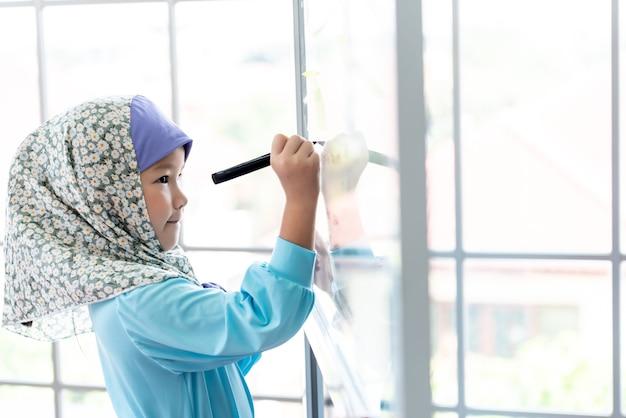 Uma menina asiática de 6 anos usando um vestido islâmico azul está escrevendo uma mensagem no quadro de vidro