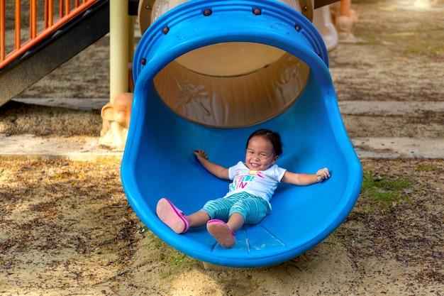 Uma menina asiática é apreciada em um equipamento de playground em uma escola.
