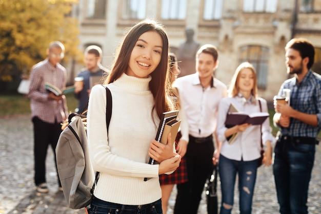 Uma menina asiática está de pé no pátio da universidade