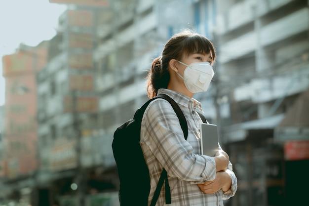 Uma menina asiática estudante usando máscara de pó pm 2.5 está em uma cidade cheia de poeira e fumaça.