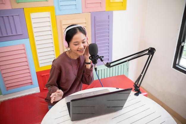 Uma menina asiática usando um fone de ouvido e um microfone enquanto usa um laptop