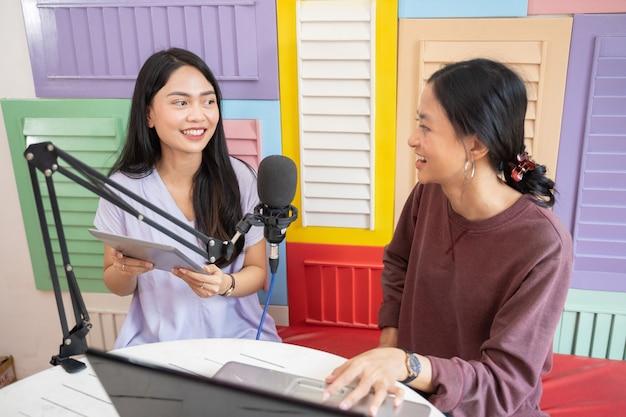 Uma menina asiática usando um tablet enquanto conversa com uma amiga em um laptop na frente de um microfone
