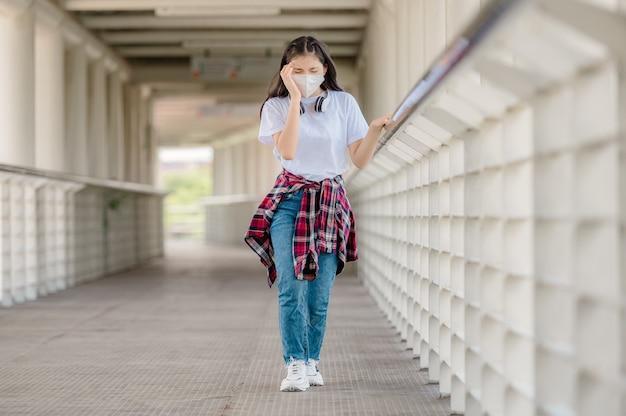 Uma menina asiática usando uma máscara caminha em um viaduto com dores de cabeça, desmaios repentinos devido a condições debilitantes e febre de coronavírus.
