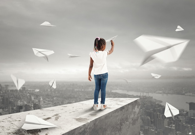 Uma menina atira aviões de papel de um telhado sobre a cidade