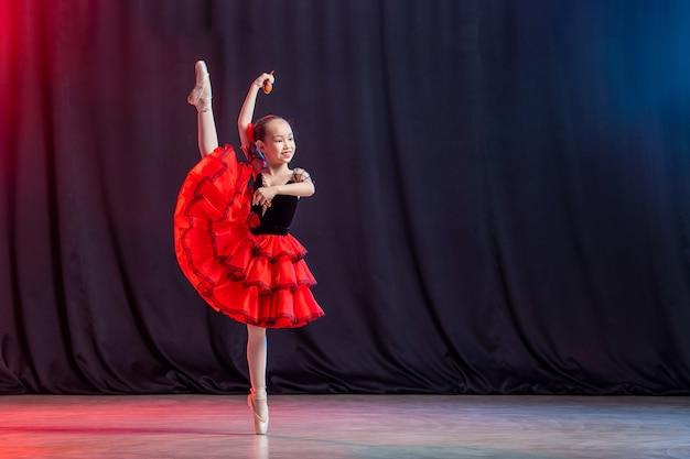 Uma menina bailarina dança no palco de tutu com sapatilhas de ponta com castanedas, a variação clássica do kitri.