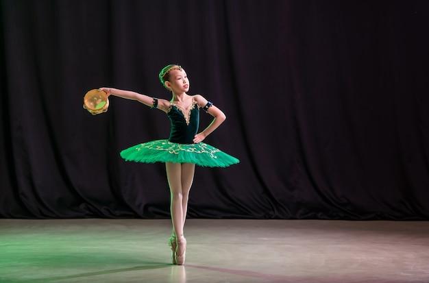 Uma menina bailarina dança no palco de tutu com sapatilhas de ponta e pandeiro, uma variação clássica da esmeralda.