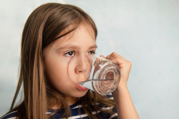 Uma menina bebe água de um copo de vidro. menina segurando um copo de água. sede de água