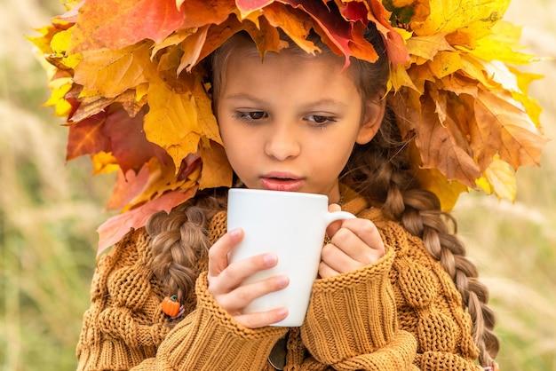 Uma menina bebe chá em um dia de outono.