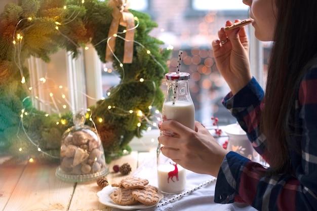 Uma menina bebe leite e come biscoitos em uma mesa perto da janela e uma coroa de árvore de natal