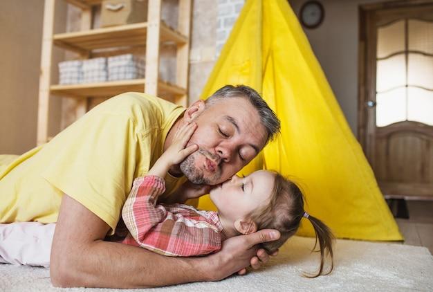 Uma menina beija seu pai feliz enquanto brincava juntos enquanto estava deitada no chão em casa. um pai carinhoso.
