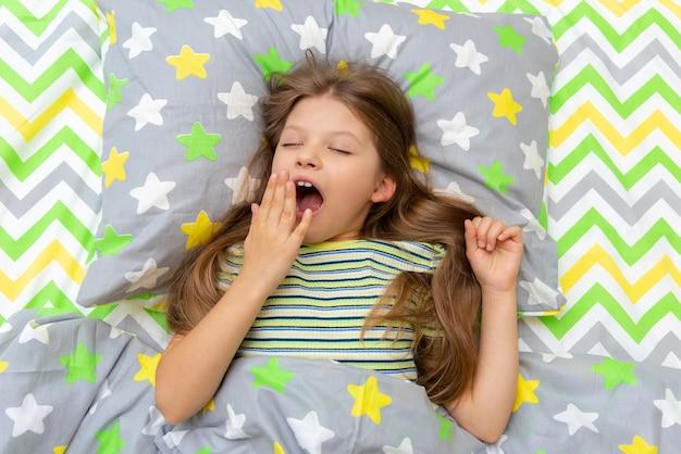 Uma menina boceja de manhã, deitada na cama.