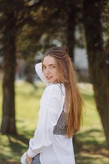 Uma menina bonita anda pela cidade sorrindo e posando