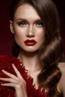 Uma menina bonita com maquiagem de noite, uma onda de cachos e lábios vermelhos, rosto de beleza