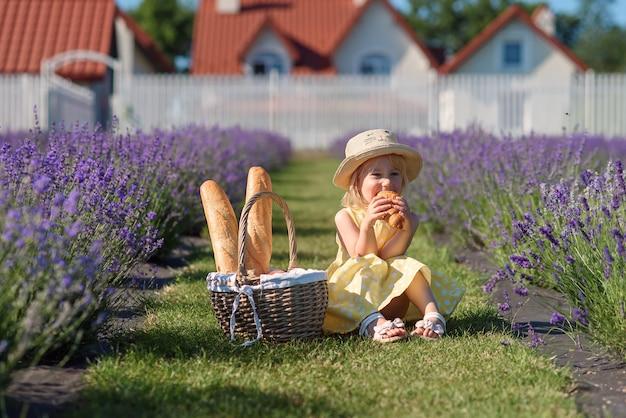 Uma menina bonita comendo em um campo de lavanda.