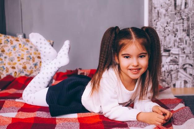 Uma menina bonita de cinco anos de idade com um penteado de dois rabos de cavalo encontra-se em uma manta vermelha em uma gaivota