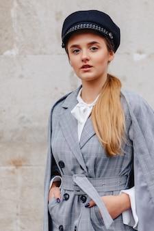 Uma menina bonita e bonita em um elegante terno anda pela cidade e poses