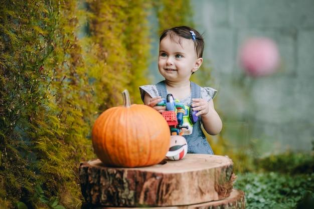 Uma menina bonita e engraçada ao lado das pisadas decorativas e da abóbora em seu quintal e sorrindo