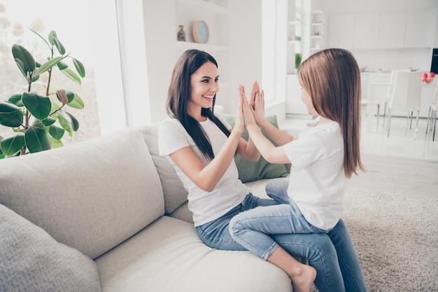 Uma menina bonita e uma jovem mamãe batendo palmas jogam jogos dentro de casa