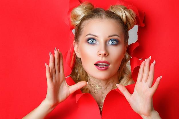 Uma menina bonita em sai de um buraco no papel vermelho