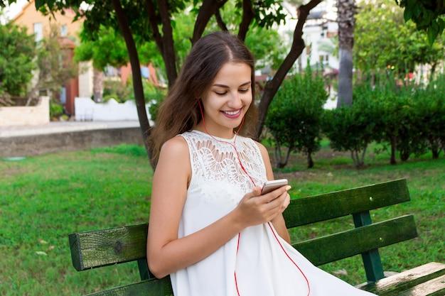 Uma menina bonita em um vestido branco está ouvindo sua música favorita no banco no parque.