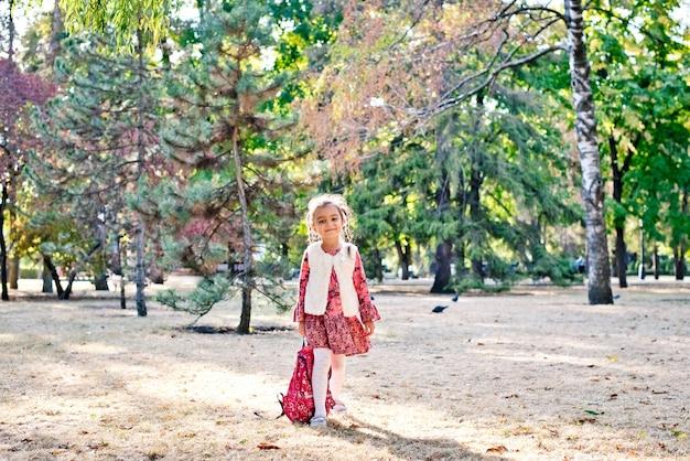 Uma menina bonita em um vestido vermelho uma estudante caminha em um parque de outono com uma mochila
