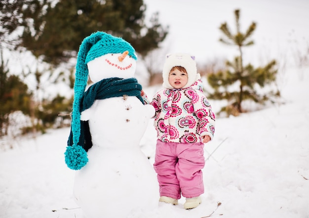 Uma menina bonita está de pé perto de um boneco de neve sorridente