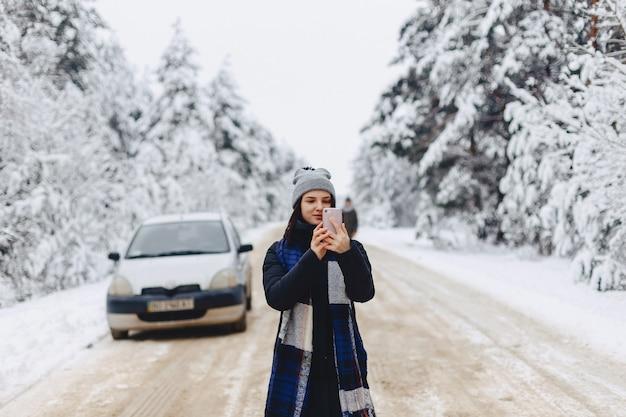 Uma menina bonita faz fotografias no telefone no meio de uma estrada de neve