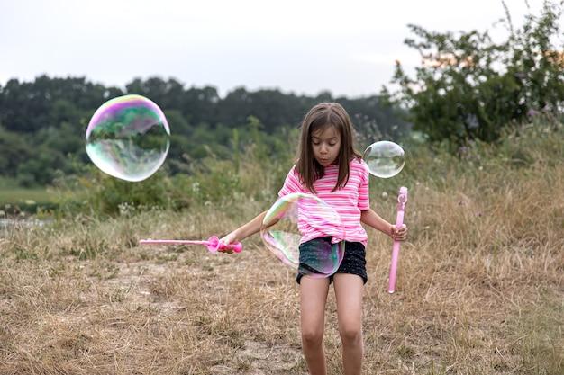 Uma menina bonita lança bolhas de sabão enormes no fundo bela natureza.