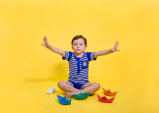 Uma menina bonita marinheiro espalhou as mãos para o lado e está sentada em um espaço isolado amarelo. a menina fez origami sem papel. barquinhos de papel colorido.