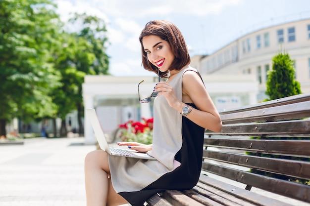 Uma menina bonita morena de vestido cinza e preto está sentada no banco na cidade. ela tem um laptop de joelhos e um sorriso amigável para a câmera.