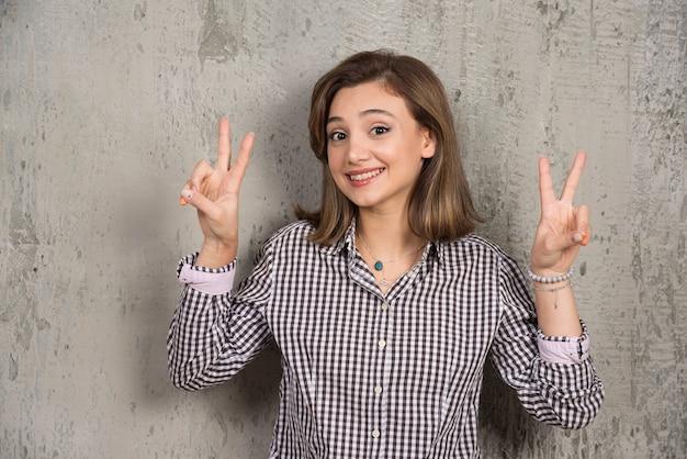 Uma menina bonita mostrando sinal de vitória de dois dedos.