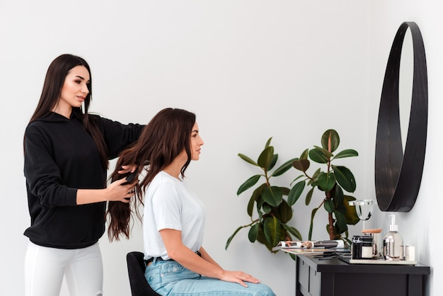 Uma menina bonita penteia cuidadosamente o cabelo do seu cliente