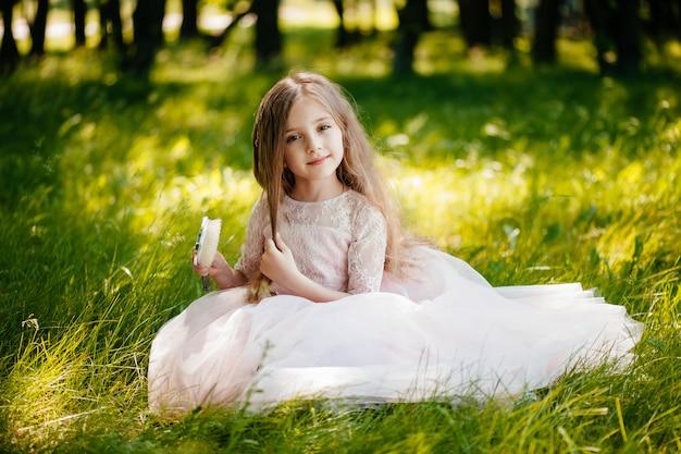 Uma menina bonita penteia o cabelo no parque.