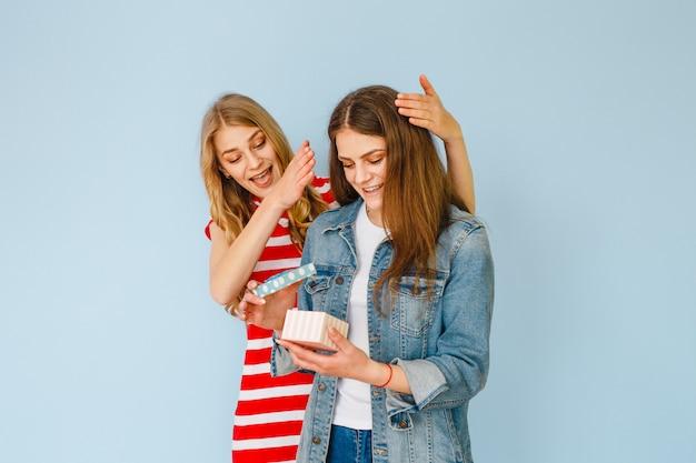 Uma menina bonita que faz um presente para sua namorada e ambos estão felizes em um fundo azul