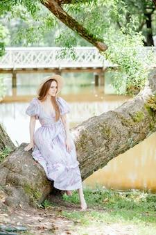 Uma menina bonita sentada na beira de uma árvore perto do rio e desvia o olhar