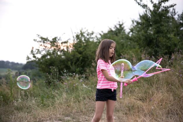 Uma menina bonita sopra bolhas de sabão no verão em um campo, atividades de verão ao ar livre.