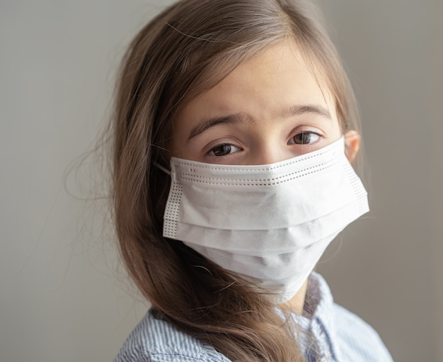 Uma menina bonitinha com uma máscara protetora descartável contra o coronavírus