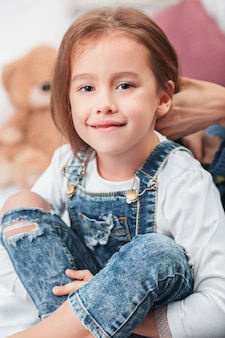 Uma menina bonitinha curtindo, brincando e criando com as mãos da mãe