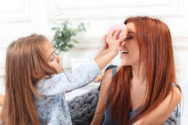 Uma menina bonitinha curtindo, brincando e criando com bolo com a mãe