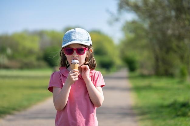 Uma menina bonitinha de óculos escuros gosta de sorvete no parque.