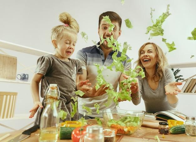 Uma menina bonitinha e seus lindos pais estão cortando vegetais