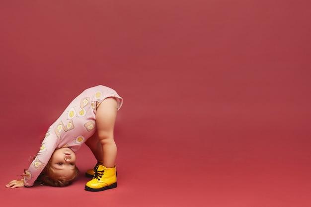 Uma menina bonitinha em elegante roupa rosa e botas amarelas está de pé na cabeça no fundo rosa
